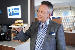 """Doug Gilmour with """"The Gloves Off Breakfast Sandwich,"""" a biscuit topped with strawberry jam, a sausage patty, scrambled eggs and cream cheese."""